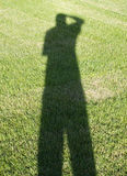Photographer shadow on grass. The shadow of the photographer on grass Royalty Free Stock Image
