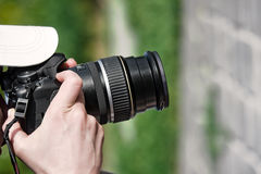 Photographer shooting. Spying with a camera, hands holding digital camera with zoom long lens Stock Image