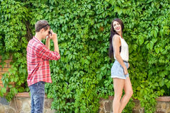Photographer shooting beautiful brunette model near green wall Royalty Free Stock Images