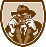 Photographer Shooting Camera Shield Retro. Illustration of a photographer shooting aiming with vintage camera facing front set inside shield crest on isolated Royalty Free Stock Photography