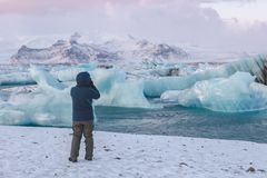Photographer shooting glacier ice in Jökulsárlón lagoon, Iceland. A photographer in a blue coat shooting glaciers on a cold winters day stock photos
