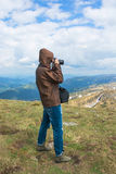 Photographer is shooting landscapes on a mountain top. Stock Image