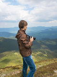 Photographer is shooting landscapes on a mountain top. Royalty Free Stock Image