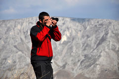 Photographer shooting pictures in the mountains. A Photographer taking pictures in the mountains Stock Photo
