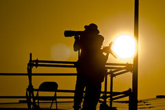 Photographer shooting at Sunset. A photographer shoots a sporting event as the sun sets Stock Photography