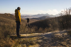 Photographer shooting sunset scene. Man photographer shooting sunset scene in the mountains Stock Photo