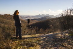 Photographer shooting sunset scene. Woman photographer shooting sunset scene in the mountains Royalty Free Stock Photo
