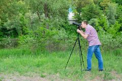 Photographer shooting from tripod against the background of river and green forest Stock Photography
