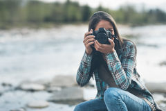 Photographer shooting. Young female photographer shooting, natural landscape on background Stock Image