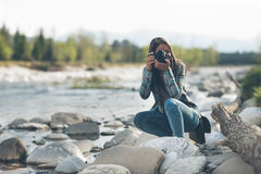 Photographer shooting. Young female photographer shooting, natural landscape on background Royalty Free Stock Image