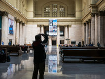 Photographer shoots Great Hall, Union Station, Chicago. Photographer holds up camera to shoot architecture in Great Hall, Union Station, Chicago, Illinois Royalty Free Stock Image