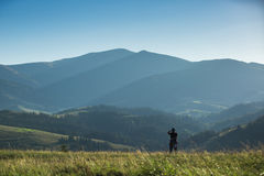Photographer shoots a mountain landscape Stock Image