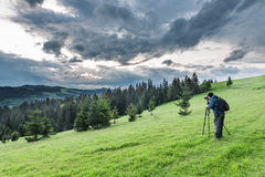 Photographer shoots a mountain landscape in the evening Stock Photo