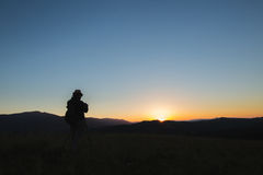 Photographer shoots a mountain landscape in the evening Royalty Free Stock Photography