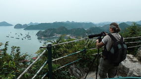 Photographer shoots on a telephoto lens. Photographer shoots View of Halong Bay from the observation deck using a telephoto lens. Full HD stock footage stock video footage