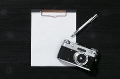 Photographer shot list. Shot list mockup. Photo session contract template. Vintage film photo camera and blank paper page on black wooden table background. Flat stock photography