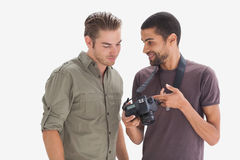 Photographer showing his friend photo on camera. On white background Stock Photos