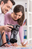 Photographer is showing to editor photos on camera. Royalty Free Stock Images
