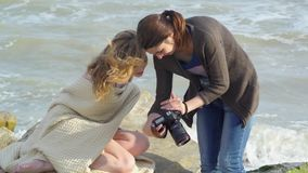 The photographer shows the photos to model. stock video