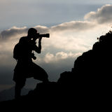 Photographer, silhouette. Silhouette of the photographer on a hillside on a background of clouds Royalty Free Stock Photo