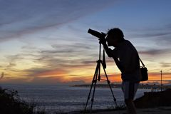 Photographer silhouette. Silhouette of the photographer with camera and tripod Royalty Free Stock Photo