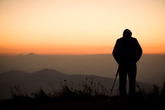 Photographer silhouette. The silhouette of a male photographer standing on a mountain, shooting a spectacular sunset Royalty Free Stock Images