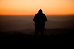 Photographer silhouette. The silhouette of a male photographer standing on a mountain, shooting a spectacular sunset stock images