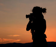 Photographer silhouette. Woman photographer silhouette and sunset Royalty Free Stock Image