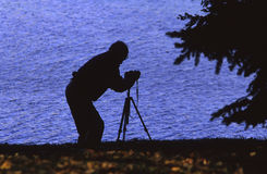 Photographer in silhouette. A photographer is silhouetted as he takes pictures Royalty Free Stock Photo