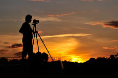 Photographer silhouette. Silhouette of a photographer shooting sunset scene Stock Photos