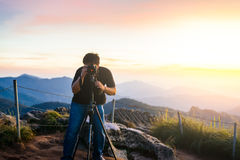 Photographer silhouette above a clouds sea, misty mountains Royalty Free Stock Photos