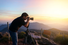 Photographer silhouette above a clouds sea, misty mountains Royalty Free Stock Photography