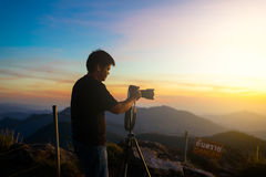 Photographer silhouette above a clouds sea, misty mountains Stock Photo