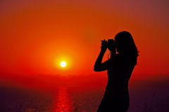 Photographer silhouette at dusk. Female photographer silhouette at dusk Royalty Free Stock Photos