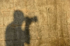 Photographer silhouette on grungy wall Stock Images