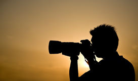 Photographer silhouette. Silhouette of a photographer holding a telephoto lens Royalty Free Stock Images