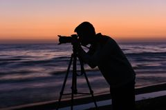 Photographer silhouette on seashore. Photographer at work, twillight Royalty Free Stock Photo