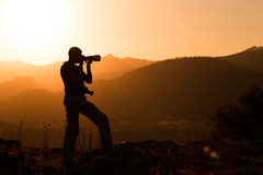 Photographer silhouette. Silhouette of a photographer shooting outdoors at sunset in the mountains Stock Image
