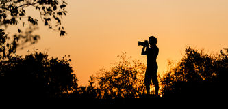 Photographer Silhouette. D against a golden sunset sky in Africa Stock Photography