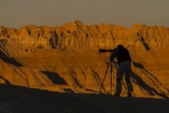 Photographer Silhouette. A photographer is silhouetted by the orange formations in Badlands National Park, South Dakota Royalty Free Stock Photo