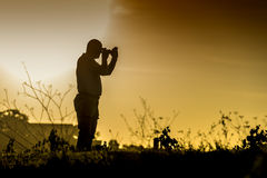 Photographer silhouette. Silhouette of a standing photographer in a landscape at sunset Royalty Free Stock Photography