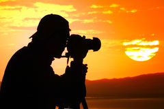 Photographer silhouette at sunset. Photographer silhouette shooting sea outdoors at sunset background Stock Images