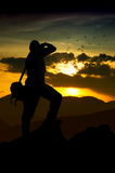 Photographer silhouette at sunset. Young photographer silhouette at sunset Royalty Free Stock Images