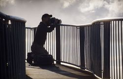Photographer in silhouette taking photographs Royalty Free Stock Photo