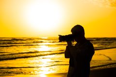 Photographer silhouette. Photographer at work on seashore Stock Images