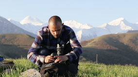 Photographer sitting and changing lenses on professional camera outdoor. stock video footage
