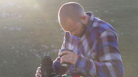Photographer sitting and changing lenses on professional camera outdoor. stock footage