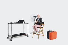 Photographer sitting on director's chair with equipments in studio Royalty Free Stock Photos