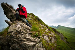 A photographer sitting on some steep rocks. A male photographer taking pictures from a steep mountain side Stock Photo