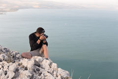 Photographer sitting stone cliff above lake sea. Royalty Free Stock Photo